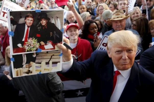 U.S. Republican presidential candidate Donald Trump holds up a photo of himself and late entertainer Michael Jackson that a memorabilia collector asked him to sign as he greets supporters after speaking at a rally with sportsmen in Walterboro